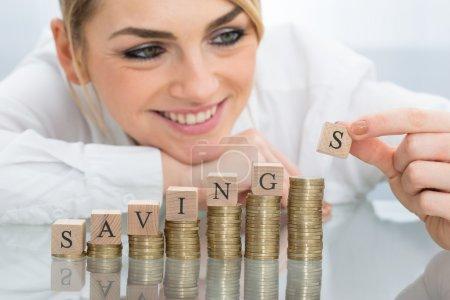 Photo pour Gros plan de la jeune femme d'affaires avec les blocs d'épargne or empilés pièces - image libre de droit