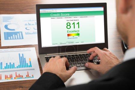 Photo pour Homme d'affaires contrôle de pointage de crédit en ligne sur ordinateur portable - image libre de droit