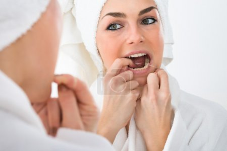 Photo pour Gros plan d'une femme regardant dans le miroir Dents de soie dentaire - image libre de droit
