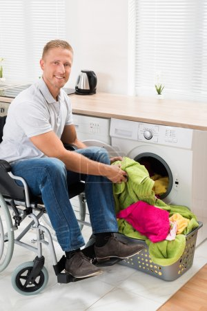 Man On Wheelchair Putting Clothes