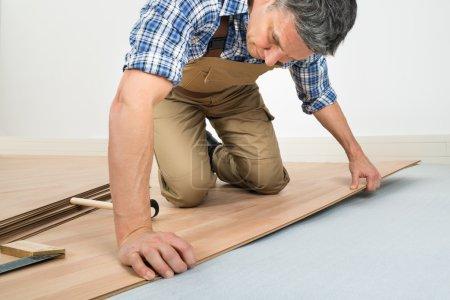 Foto de Hombre instalando nuevo piso de madera laminado en casa - Imagen libre de derechos