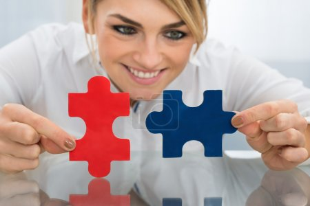 Businesswoman Holding Pieces Of Jigsaw Puzzle