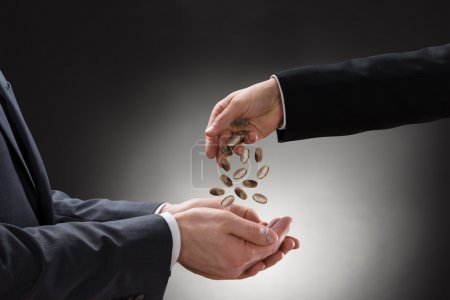Businessman Pouring Coins On Colleague Hand