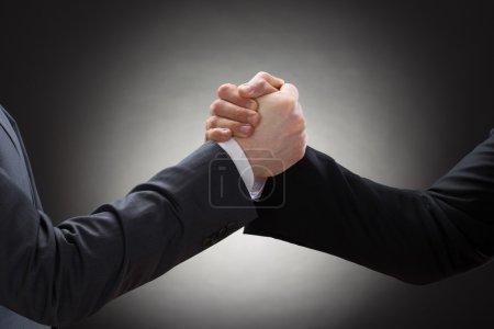 Two Businessmen Arm Wrestling