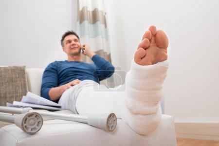 Foto de Hombre con la pierna fracturada sentado en el sofá hablando por teléfono móvil - Imagen libre de derechos