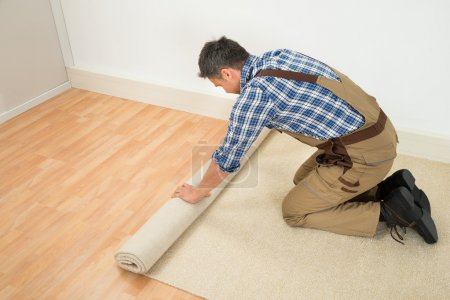 Photo for Male Worker Unrolling Carpet On Floor At Home - Royalty Free Image