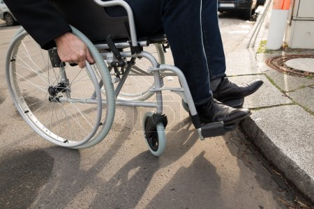 Photo for Close-up Of Disabled Man Sitting On Wheelchair On Street - Royalty Free Image