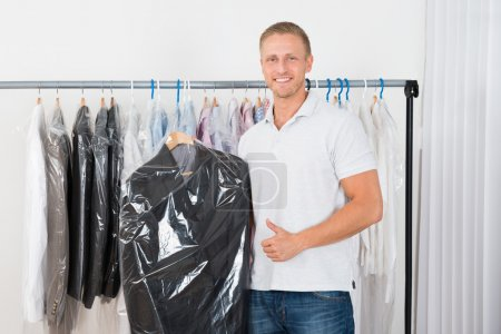 Photo for Young Happy Man Standing With Coat In Dry Cleaning Store gesturing thumb up - Royalty Free Image