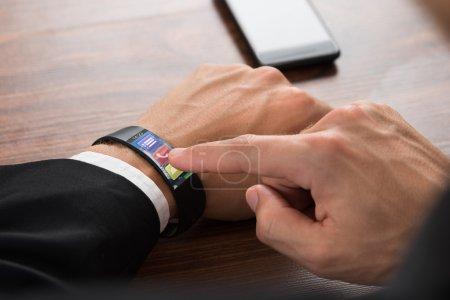 Photo pour Gros plan de la main de l'homme d'affaires portant Smartwatch appuyant sur le bouton d'appel - image libre de droit