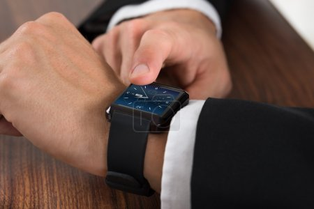 Photo for Close-up Of A Businessman Checking Time On Wrist Watch - Royalty Free Image
