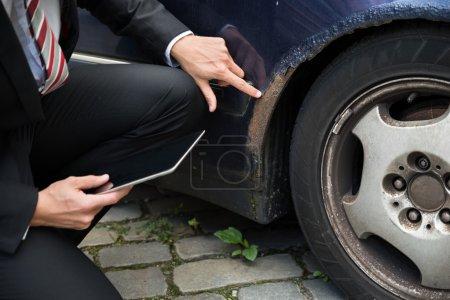 Insurance Agent  Examining Damaged Car