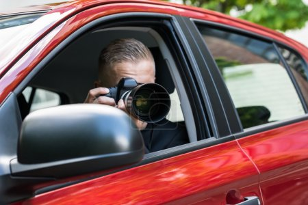 Man Photographing With Camera From Car