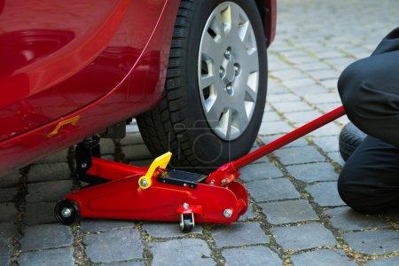 Photo pour Voiture levée avec Jack de plancher hydraulique rouge pour la réparation - image libre de droit