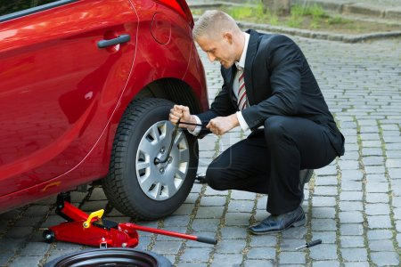 Man Changing Wheel With Spanner