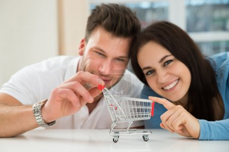 Photo for Close-up Of Smiling Young Couple With Miniature Empty Shopping Cart - Royalty Free Image