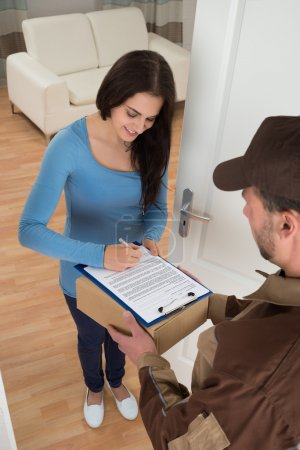 Woman Signing While Receiving Courier
