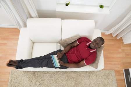 Photo for High Angle View Of African Man On Couch Using Digital Tablet - Royalty Free Image
