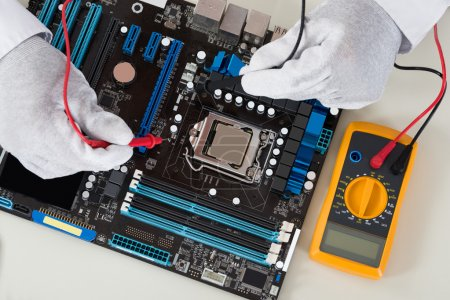 Photo for Close-up Of Person Hands Checking Motherboard With Multimeter - Royalty Free Image