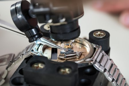 Photo for Close-up Of Loupe And Tweezers Over Wristwatch - Royalty Free Image