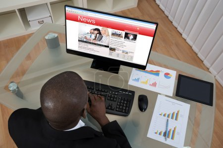 Photo for Young African Businessman Looking At Business News On Computer In Office - Royalty Free Image
