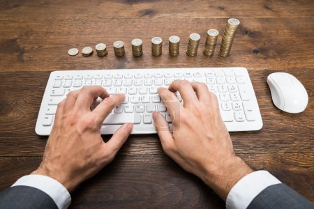 Photo for Businessman Hands Using Keyboard In Front Of Stacked Coins - Royalty Free Image