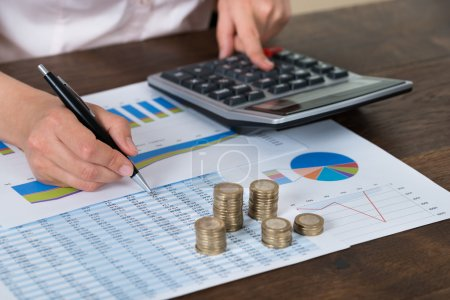 Businessperson With Coins Over Graph