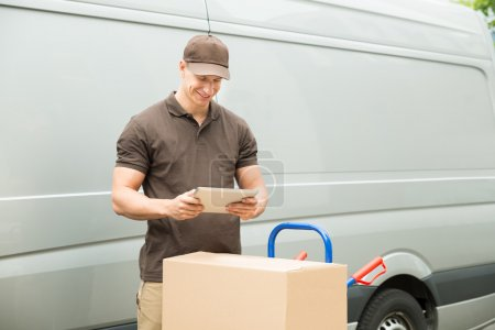 Photo for Young Happy Delivery Man With Digital Tablet And Cardboard Boxes - Royalty Free Image