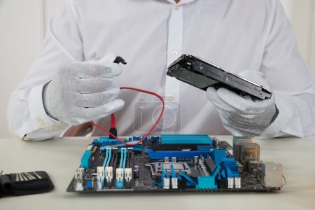 Photo for Close-up Of Male Technician With Motherboard And Harddisk - Royalty Free Image