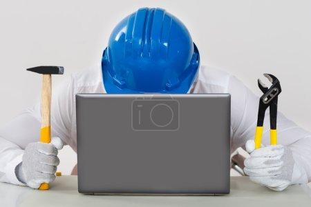 Photo pour Technicien masculin dans Hardhat tenant le marteau et la pince avec l'ordinateur portable au bureau - image libre de droit