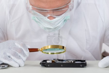 Man With Harddisk And Magnifying Glass
