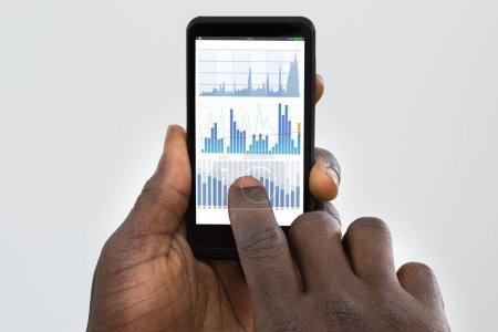 Photo pour Gros plan des mains de personne à l'aide de téléphone portable avec graphique sur écran - image libre de droit