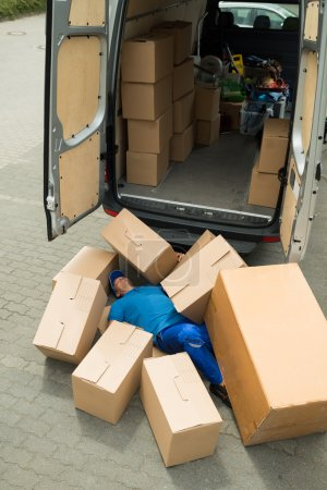 Photo for Unconscious Male Worker Lying On Street Surrounded With Boxes - Royalty Free Image