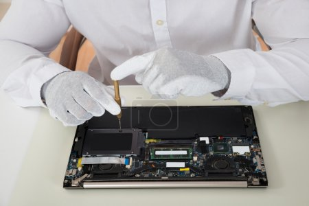 Photo for Close-up Of Technician Repairing Laptop At Desk - Royalty Free Image