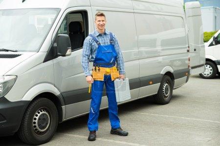 Photo pour Jeune réparateur avec outils et boîte à outils debout devant le fourgon de service - image libre de droit