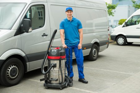 Happy Male Cleaner In Blue Uniform Standing With V...