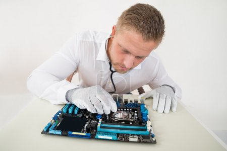 Photo for Technician Listening To Cpu Processor In Motherboard With Stethoscope - Royalty Free Image