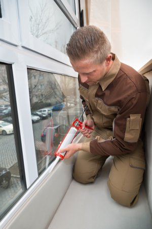 Worker Applying Glue With Silicone Gun
