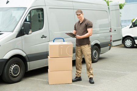 Photo for Young Happy Delivery Man With Cardboard Boxes Writing On Clipboard - Royalty Free Image