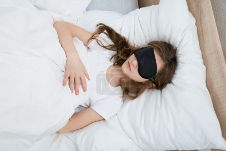 Photo for Girl Sleeping On Bed With Black Sleep Mask In Bedroom - Royalty Free Image