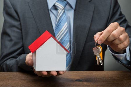 Businessman With Keys And House Model