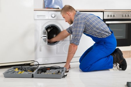 Worker With Toolbox Repairing Washing Machine