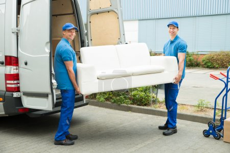 Photo for Two Happy Male Workers Putting Furniture And Boxes In Truck - Royalty Free Image
