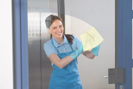Female Janitor Cleaning Glass