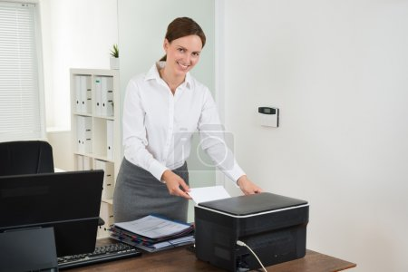 Secretary Inserting Paper In Printer
