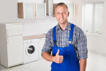 Photo for Young Happy Repairman Showing Thumbs Up Sign In Kitchen - Royalty Free Image