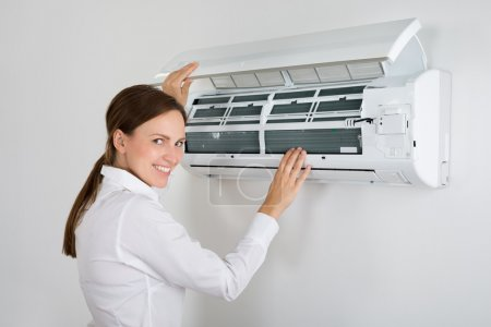 Businesswoman Checking Air Conditioner