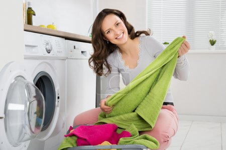 Woman Laundering Clothes In Washer