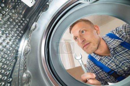 Repairman Looking Inside The Washing Machine