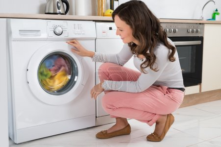 Woman Looking At Clothes Rotating Inside The Washing Machine