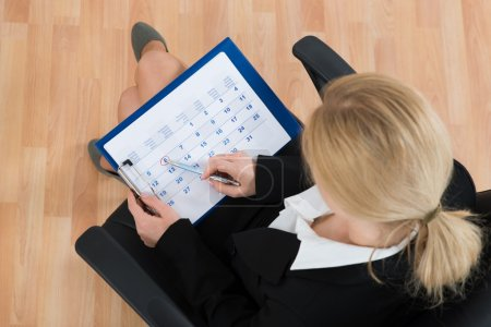 Photo for Close-up Of Businesswoman Marking Date With Pen On Calendar - Royalty Free Image